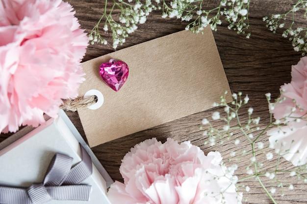 ギフトボックスとカーネーションの花のある空の紙タグ