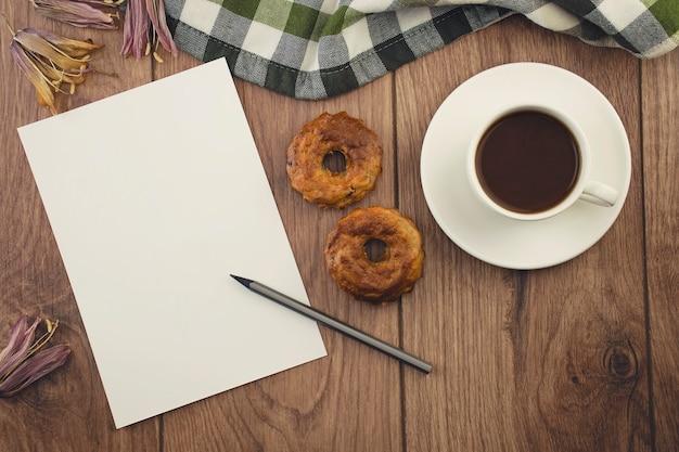 Чистый лист бумаги с карандашом, чашка кофе с кексами на деревянном столе.