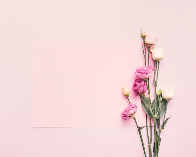 Blank paper with bright flowers on table