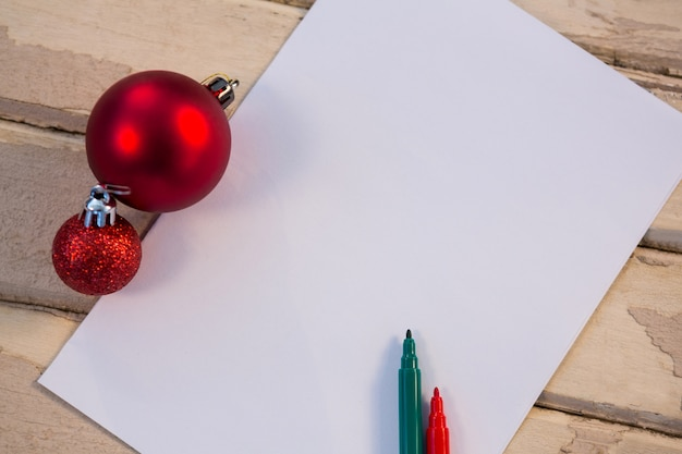 Blank paper with christmas balls and colored pencils