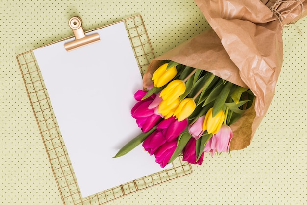 Blank paper with clipboard and bouquet of tulip flowers over yellow polka dot background