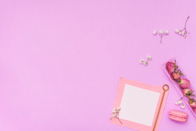 Чистый лист бумаги с сухими розами и миндальное печенье