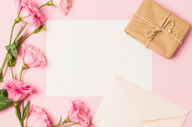Blank paper with envelop; fresh pink flower and brown wrapped gift box over pink background
