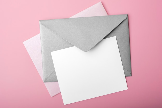분홍색 배경에 봉투와 빈 종이입니다. 디자인을위한 빈 카드, 모의