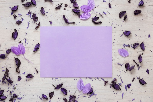 Blank paper with flower petals and leaves on table