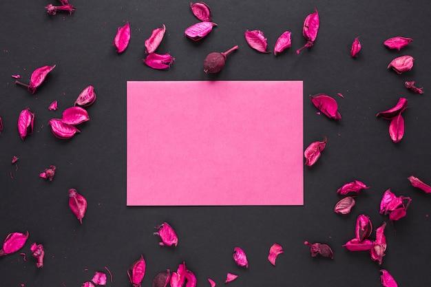 Чистый лист бумаги с лепестками цветов на столе