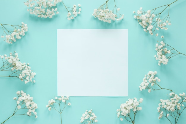 Blank paper with flowers branches on table