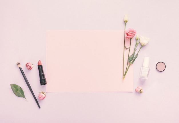 Blank paper with flowers, nail polish and lipstick on table