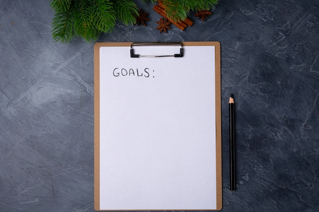 Blank paper with goals title and black pencil on grey table.