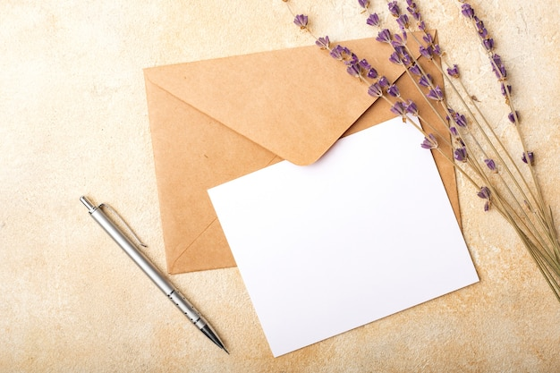 Blank paper with kraft envelope and lavender flowers on a light background. clean postcard for your signatures