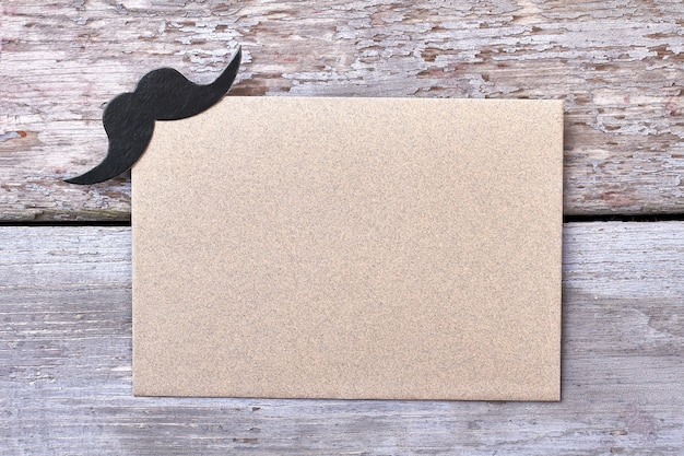 Blank paper with mustache. empty paper on wooden background. create your party invitation.