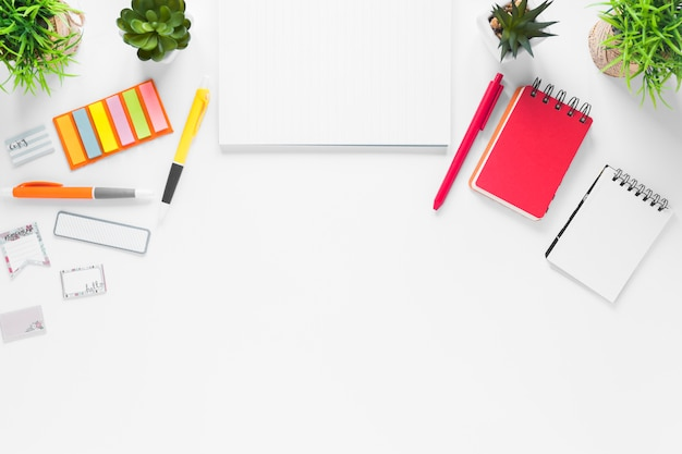 Blank paper with office supplies and plant pots on white backdrop