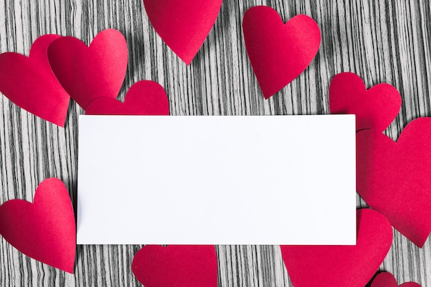 Blank paper with paper hearts on wood