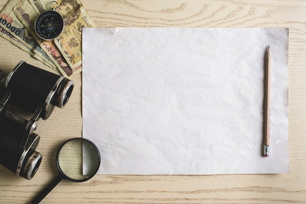 Blank paper with pencil and adventure objects