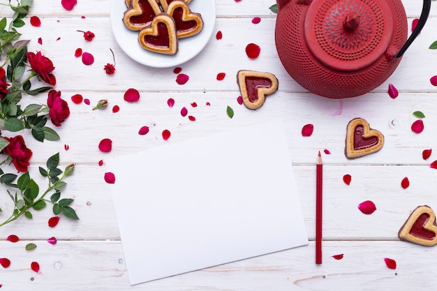 Blank paper with red rose petals on a white surface near a red teapot and heart-shaped cookies