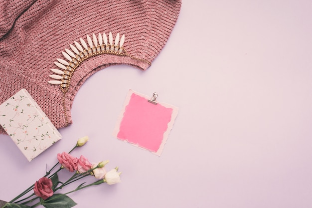 Blank paper with rose flowers, necklace and sweater on table
