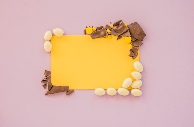 Blank paper with small candies and cracked chocolate