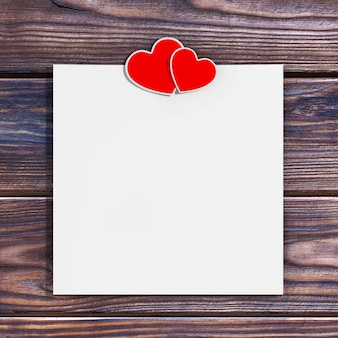 Blank paper with two hearts on a wooden table. 3d rendering