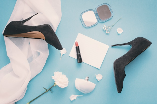 Blank paper with woman shoes and lipstick on table