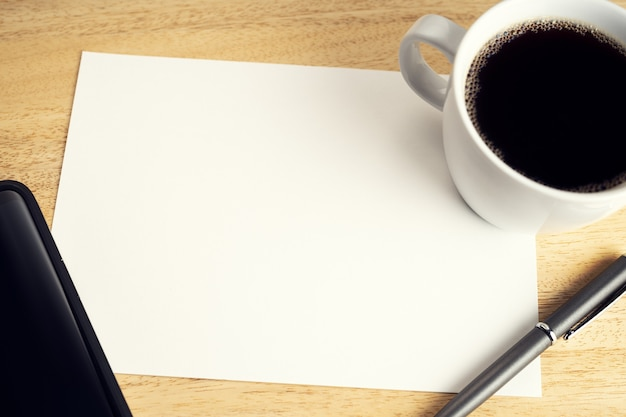 Blank paper on wooden desk table with cup of coffee, pen and smartphone. mock up template. study or business concept