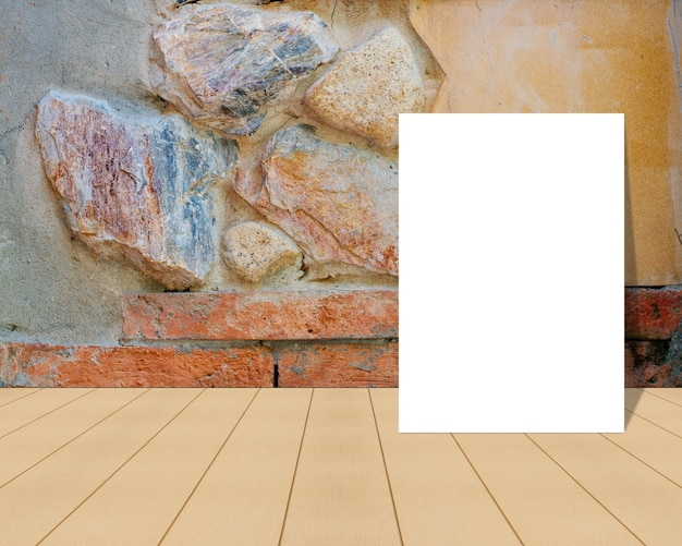 Blank paper on a wooden surface and a rock wall
