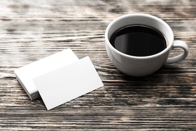 Чистые бумаги и чашка кофе на деревянном столе