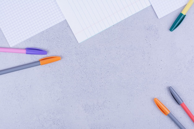 Blank papers and multicolor pencils on grey.