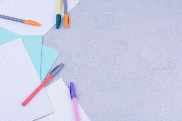 Documenti in bianco e penne multicolori isolate sulla superficie grigia