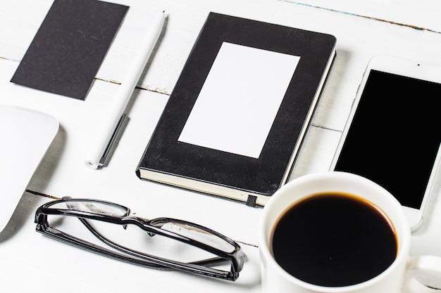 디자이너를위한 빈 서류 템플릿입니다. 빈티지 나무 배경에 응답 디자인 모형. 종이, 레터 헤드, 커피 컵, 스마트 폰, 연필 및 나무로되는 테이블 배경에 헤드폰. 평면도.