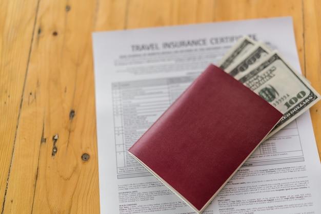 旅行航空保険申込書の上に木製のテーブルに米ドルの空白のパスポート。