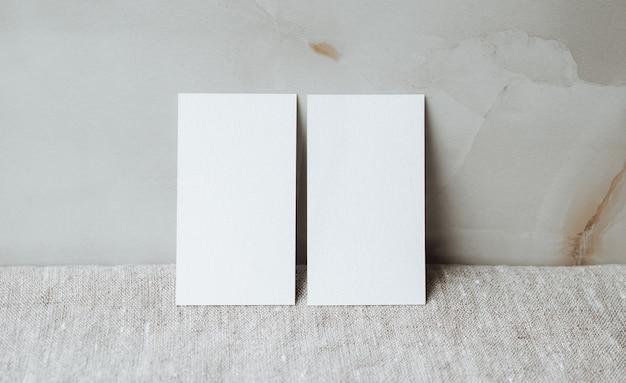 灰色のリネンのテーブルクロス生地の背景に空白のパーソナルカードの文房具のモックアップ
