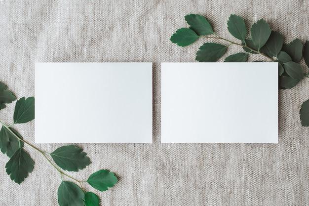 灰色のリネンに自然光と植物の影が付いた空白のパーソナルカードステーショナリーモックアップ