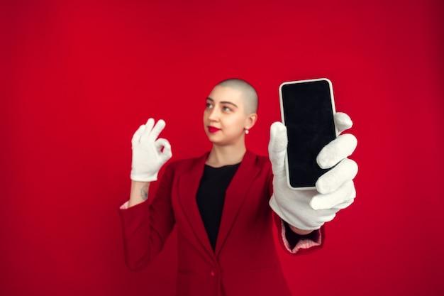 空白の電話の画面。赤い壁に隔離された若い白人ハゲ女性の肖像画。手袋をはめた美しい女性モデル。人間の感情、顔の表情、販売、広告のコンセプト。気紛れな文化。