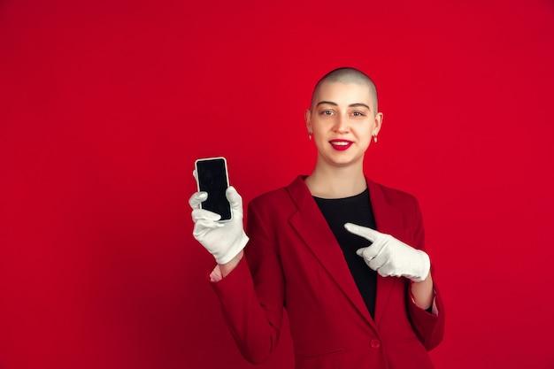 空白の電話の画面。赤い壁に隔離された若い白人のハゲの女性の肖像画。手袋をはめた美しい女性モデル。人間の感情、顔の表情、販売、広告のコンセプト。気紛れな文化。