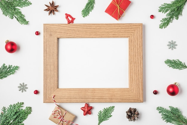 Blank photo card in frame made of fir tree branches gift boxes decorations