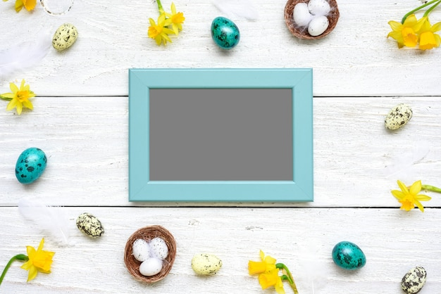 Blank photo card in frame made of quail eggs, spring flowers and feathers on white wooden table