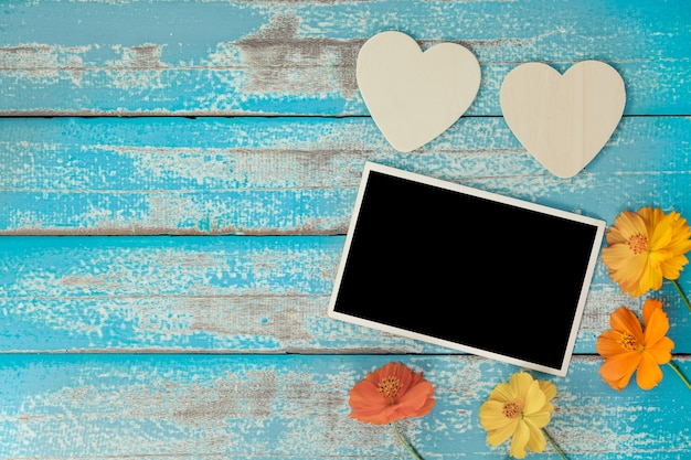 Blank photo frame album decorate with flower and heart shape on old blue wood background