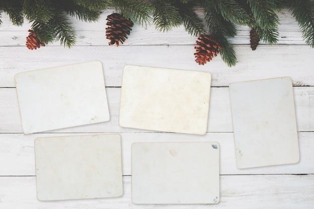 空の写真フレームアルバム - クリスマスの木のテーブルの空の古いインスタント写真のペーパー。トップビュー、ヴィンテージ、レトロスタイル