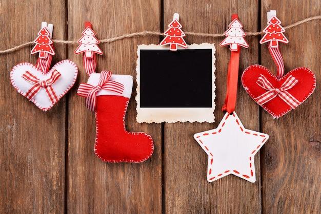 Пустая фоторамка и рождественский декор на веревке, на деревянном