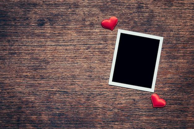 Пустая рамка фото и красное сердце на фоне дерева с пространством.