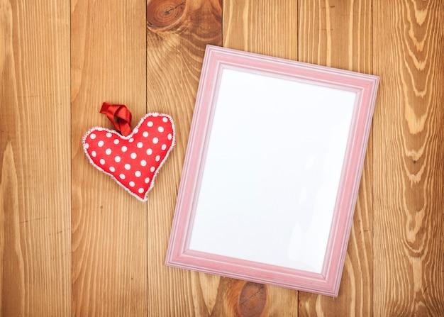 빈 사진 프레임과 빨간 발렌타인 하트 장난감. 나무 배경에