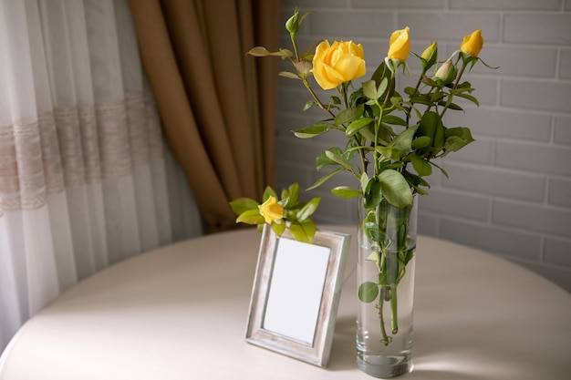 흰 벽 위에 서있는 꽃병에 빈 사진 프레임과 노란 장미