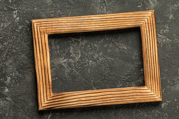 Blank photo frame on black concrete .