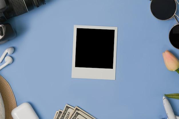 Пустая рамка для фотографий, камера, чашка и солнечные очки на синем фоне.