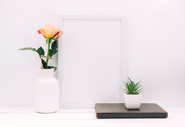 Blank photo frame; diary; plant with rose on white table