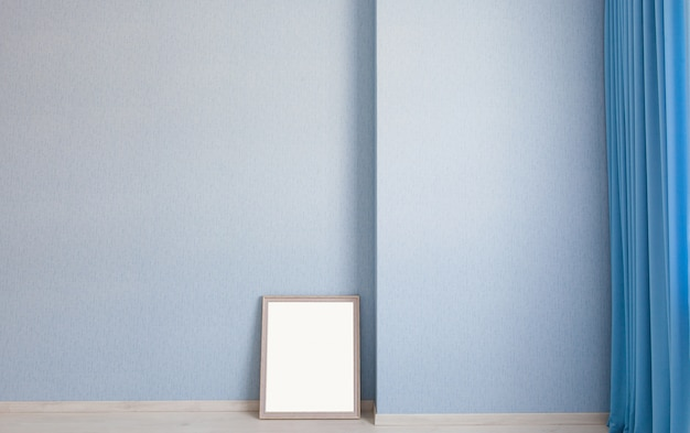 Blank photo frame on the floor, leaning on blue wall of living room with curtains and wooden parquet.