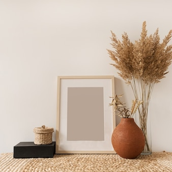 Blank photo frame, fluffy reeds bouquet in vase, rye in clay pot at white wall