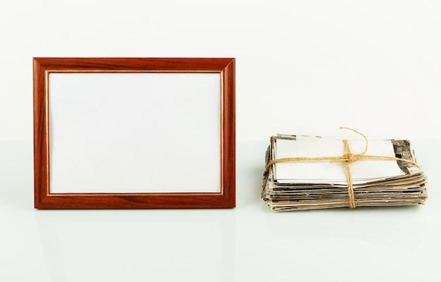 Пустая фоторамка для фотографий, цветок в горшке, стопка старых фотографий на столе.