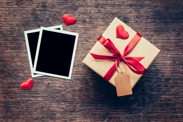 Blank photo frame and gift box with red heart on wood background.