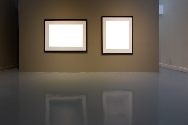 Blank photo frame on golden wall in art gallery.